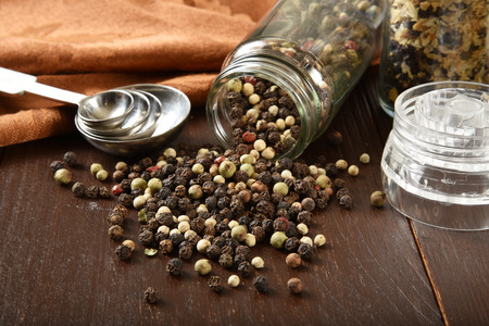 White and black peppercorns spilling out of a spice bottle
