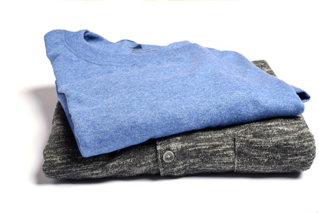 A folded t-shirt and sweater on a white table