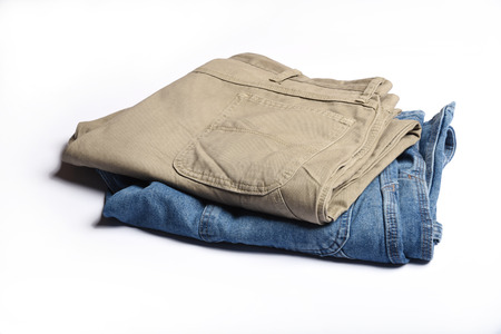 khaki pants: Two pair of folded jeans on a white background