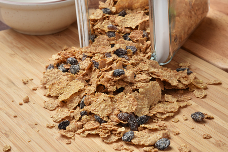 canister: Bran and raisin cereal spilling out of a glass canister Stock Photo