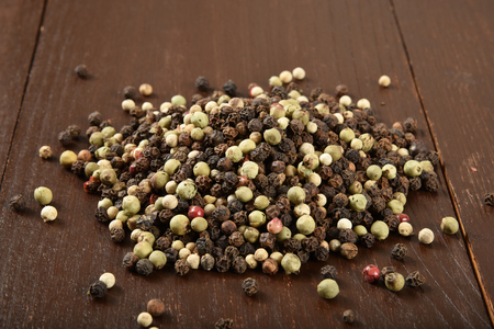 A mound of white and black peppercorns on a rustic wooden table