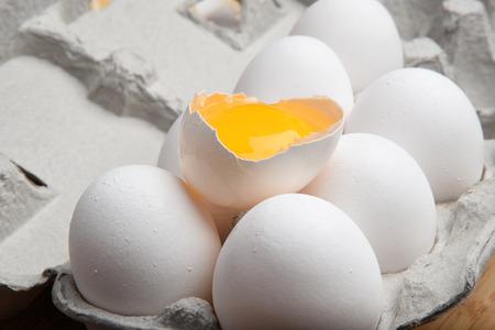 broken up: A carton of eggs with an egg broken up on top Stock Photo