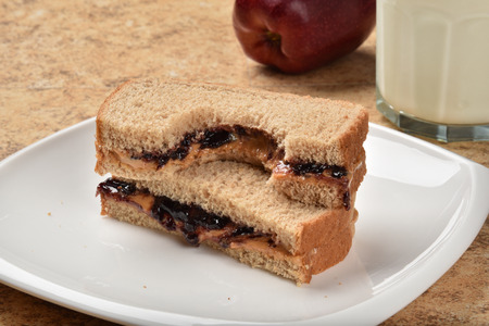 strawberry jam sandwich: A peanut butter sandwich with a bite out of it