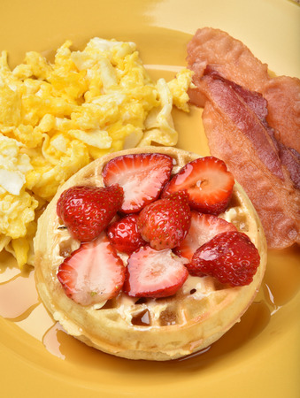 Overhead view of waffles with strawberries, bacon and scrambled eggs