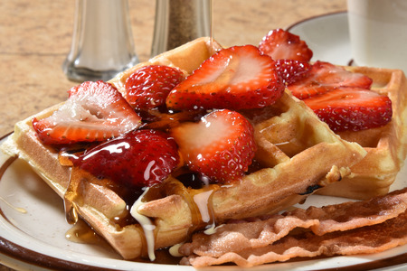 Belgiam waffles with crispy bacon and sliced strawberries