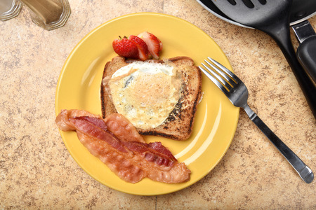 overhead view: Overhead view of a fried egg in the hold with crispy bacon strips Stock Photo