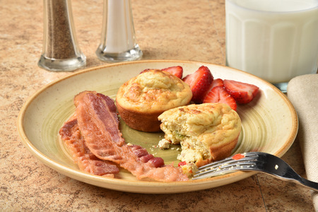Golden frittatas with bacon strips and sliced strawberries Stock Photo