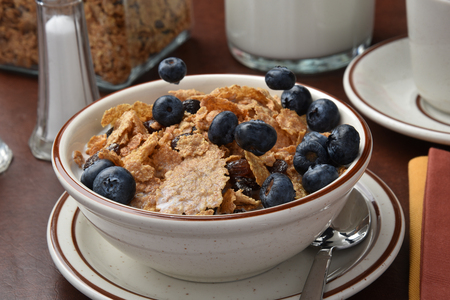 freeze dried: Freeze mortion shot of blueberries being dropped onto a bowl of cereal Stock Photo