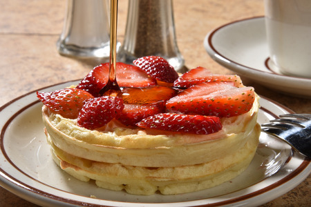 maple syrup: Pouring maple syrup onto waffles with sliced strawberries