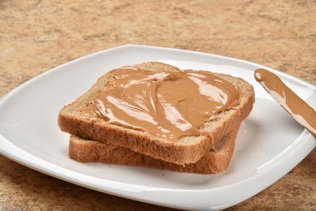 Romige pindakaas verspreid op volkoren brood