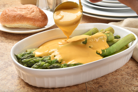 Ladeling Hollandaise sauce onto hot steamed asparagus Stock Photo