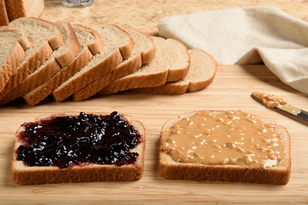 peanut butter and jelly: Making a peanut butter and jelly sandwich on a cutting board