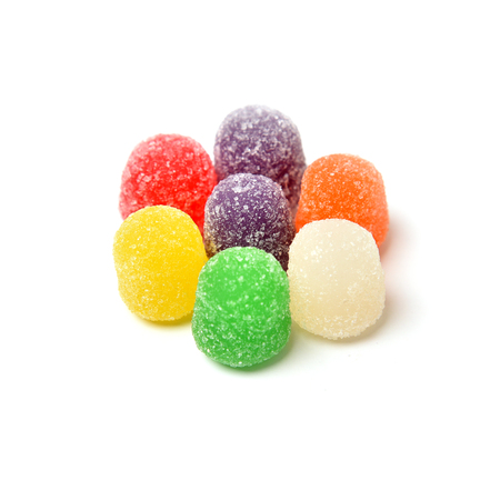 A circle of multi flavored gumm drops on a white background