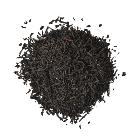 A mound of loose leaf black tea on a white background
