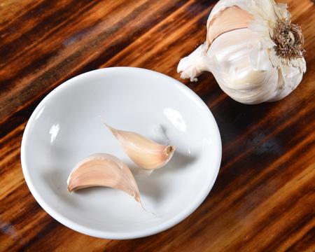 Fresh garlic bulb and cloves in a spice bowl