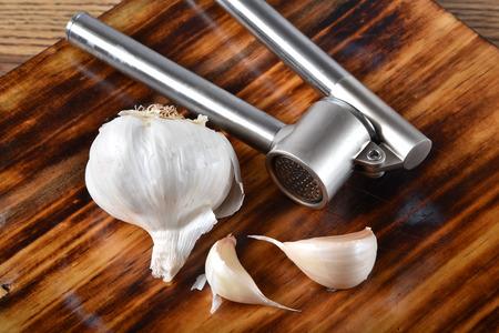 A bulb of garlic and a garlic press on a cutting board Stock fotó