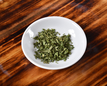 Dried parsley flakes in a small bowl on a cutting board