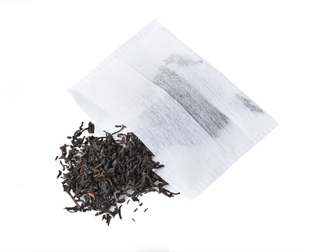 A mound of whole leaf black tea with a disposable tea bag from an overhead view