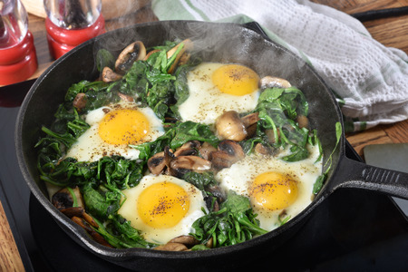 Cooking spinach, mushroom and egg hash in a cast iron skillet Фото со стока