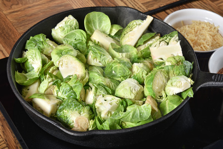 Brussels sprouts simmering in a cast iron skillet