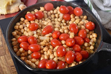 ソテーひよこ豆とバック グラウンドでチキンと鋳鉄のフライパンでブドウのトマト
