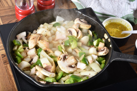 Sauteing onionis, mushrooms, garlic and diced green peppers in a cast iron skillet