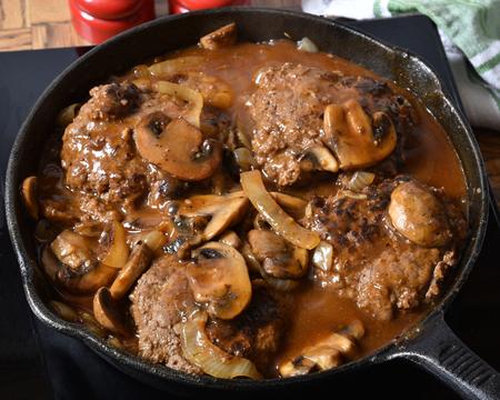 Salisbury steak with mushroom gravy in a cast iron skillet