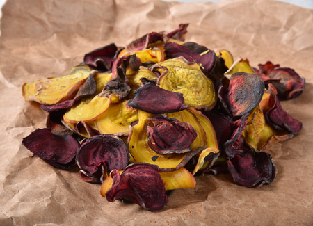 Home made baked beet chips on a brown paper wrapper