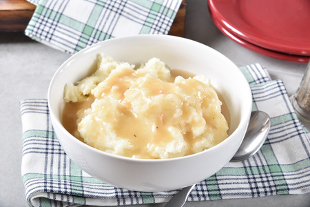 A serving bowl of mashed potatoes topped with chicken gravy