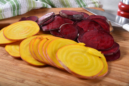 Thin sliced red and gold beets on a cutting board