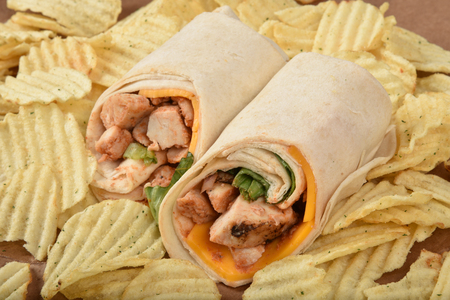 A chicken wrap sandwich with cheddar cheese on a mound of potato chips.  High angle view 版權商用圖片