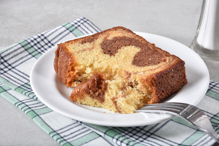 A slice of marble cake with a missing bite on a plate
