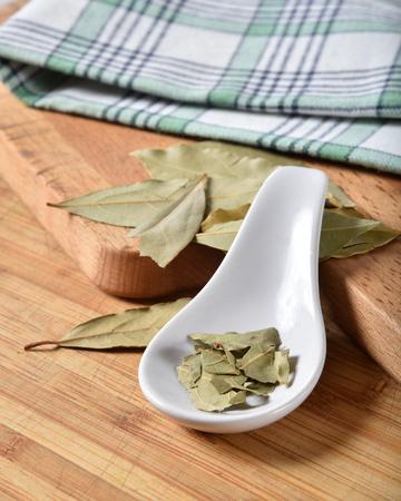 Crushed bay leaves in a ceramic spoon on a cutting board