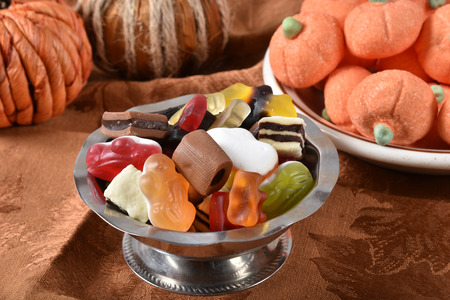 A candy dish of gelatin fruit candies, chocolates, and pumpkin marshmallows in the background for Halloween Stock Photo