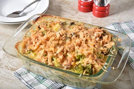 Gourmet homemade green bean and broccoli casserole topped with cheese and french fried onions. Stock Photo