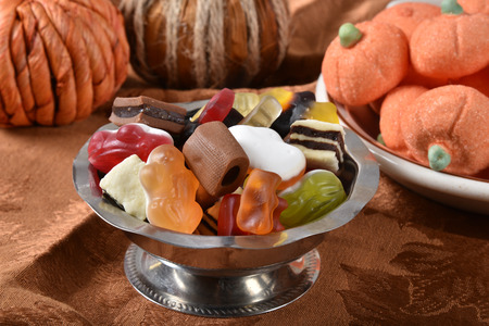 A silver candy dish with gummies and other candies, with marshmallow pumpkins Stock Photo