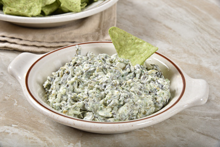Bowl of delcious sour cream and spinach dip with guacamole flavored tortilla chips.