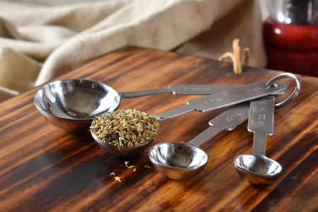 A teaspoon full of dried oregano leaves on a wooden cutting board