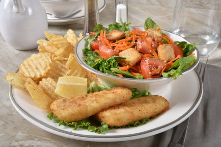 Breaded fish sticks with potato chips and a garden salad.