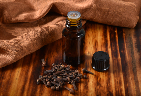 A bottle of clove essential oil with whole cloves