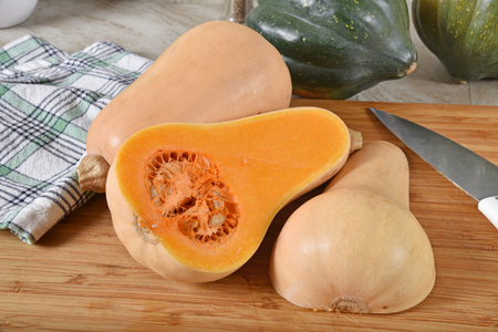 Fresh uncooked butternut and acorn squash on a cutting board.