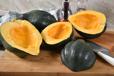 Acorn squash cut in half with the seeds removed on a cutting board