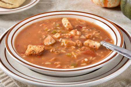 Closeup of a bowl of chicken gumbo with rice and croutons