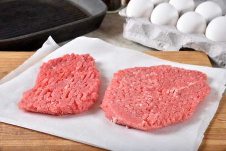 Uncooked cube steaks on a cutting board near a cast iron grill and a carton of eggs 免版税图像