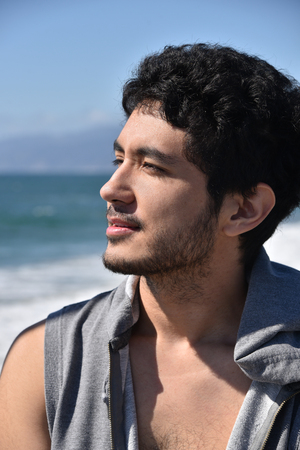A handsome dark complected young man enjoying the view at the ocean Stock Photo