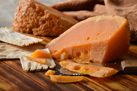 A wedge of gourmet mimolette cheese on a cutting board with artisan crackers