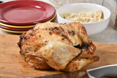 A fresh baked whole chicken on a cutting board with mashed potatoes in the background