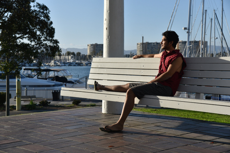 Handsome young man sitting on a bench looking over the marina in the late afternoon sunlight