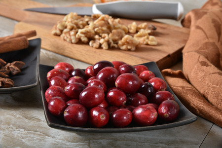 A bowl of fresh cranberries with star anise, cinnamon sticks and chopped walnuts,