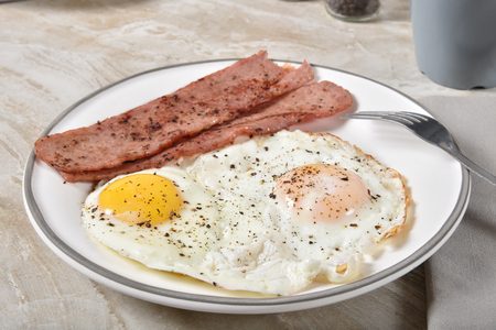 Delicious fried egg breakfast with crispy strips of turkey bacon 写真素材